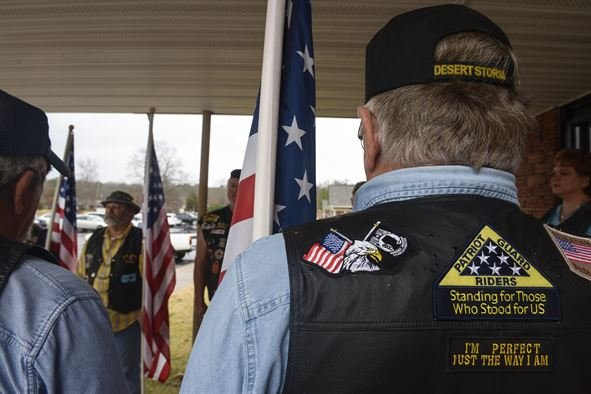 The Patriot Guard Riders stand pay their respects at a service.